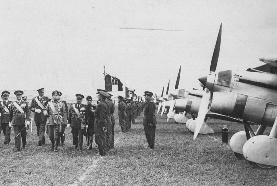 Italian fascist dictator Benito Mussolini (fourth from left) marches with officers past an air combat troop and their planes during armaments show in 1940. Photo: Time Life Pictures, Time & Life Pictures/Getty Image / Time Life Pictures