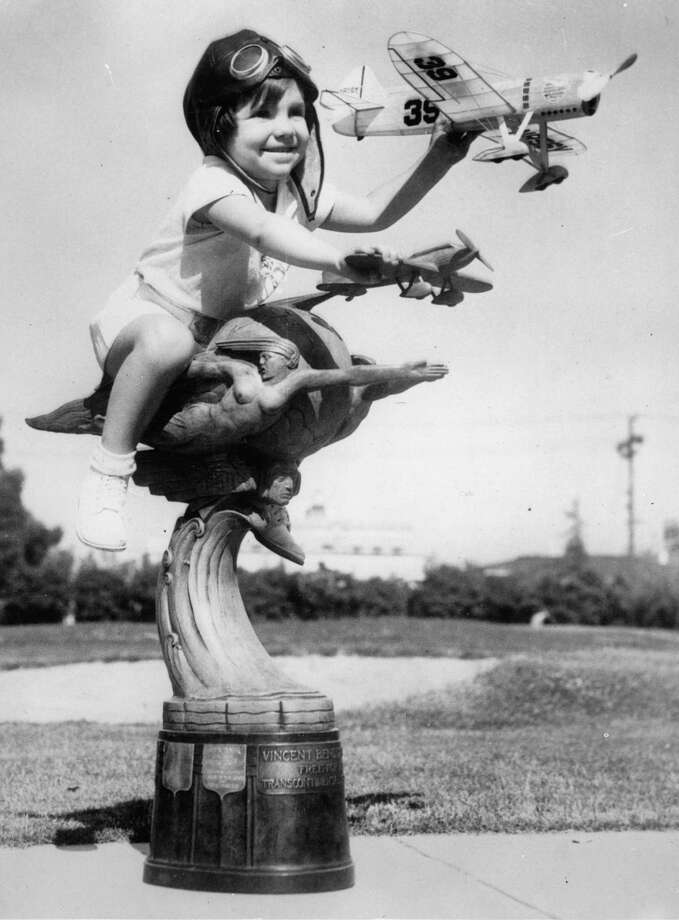 A girl at sit on a trophy, playing with two flying models during an air show in Los Angeles, circa 1930. Photo: Imagno, Getty Images / 2010 Getty Images