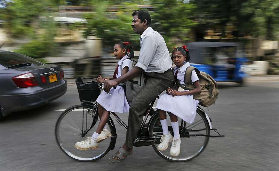 Riding with Dad:An ethnic Tamil man bikes his daughters to school in Colombo, Sri Lanka. Photo: Eranga Jayawardena, Associated Press