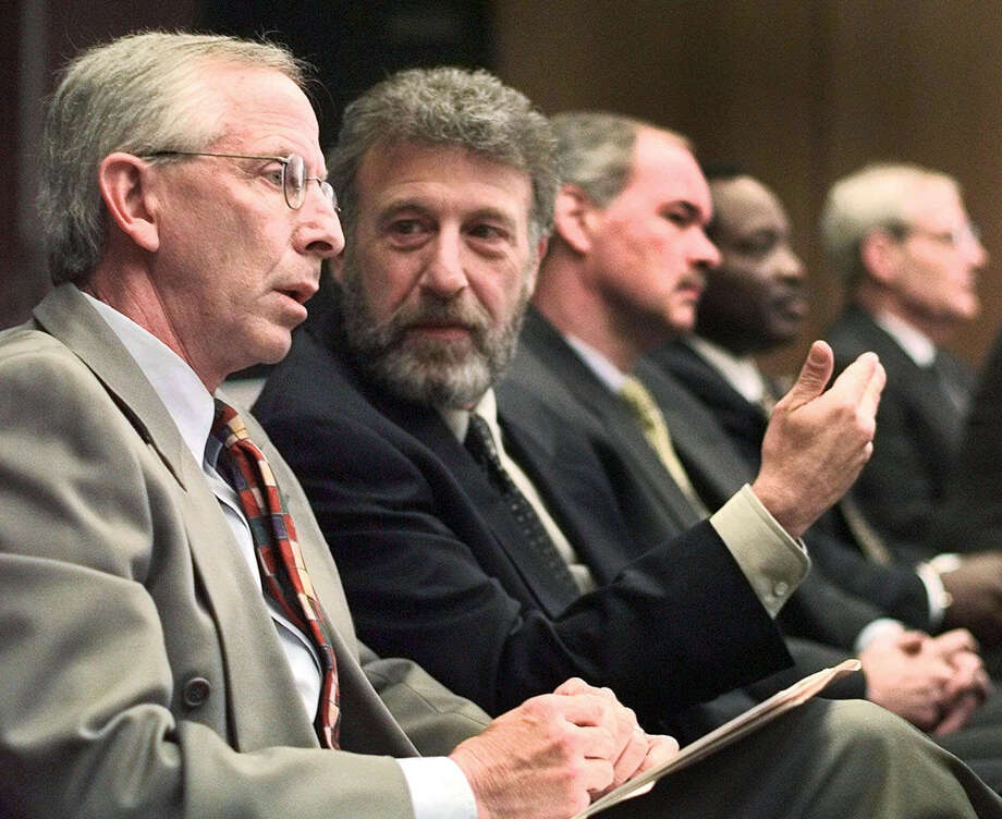 FILE - In this Thursday, May 6, 1999 file photo, George Zimmer, second from left, gestures to Andy Dolich prior to a meeting, in Oakland, Calif. Men's Wearhouse Inc. says it has dismissed Zimmer, its founder and executive chairman. In a terse release issued Wednesday, June 19, 2013, the company didn't give a reason for the abrupt firing of Zimmer, who built Men's Wearhouse from one small Texas store using a cigar box as a cash register to one of the nation's largest specialty retailers in men's clothing, with 1,143 locations. (AP Photo/Ben Margot, File) Photo: Ben Margot