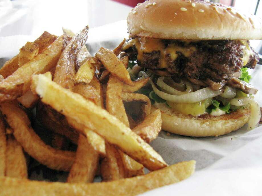 The Fattboy with cheese features a half-pound of meat at Fattboy Burgers & Dogs. Fries  are cooked in peanut oil. Photo: Express-News File Photo