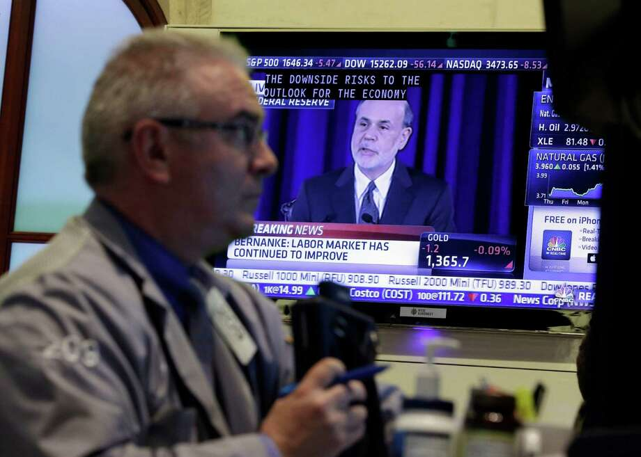 Fed Chairman Ben Bernanke is on a television screen as trader James Dresch works in a booth on the floor of the New York Stock Exchange Wednesday, June 19, 2013.  The Federal Reserve offered a hint Wednesday that it's moving closer to slowing its bond-buying program, which is intended to keep long-term interest rates at record lows. (AP Photo/Richard Drew) Photo: Richard Drew
