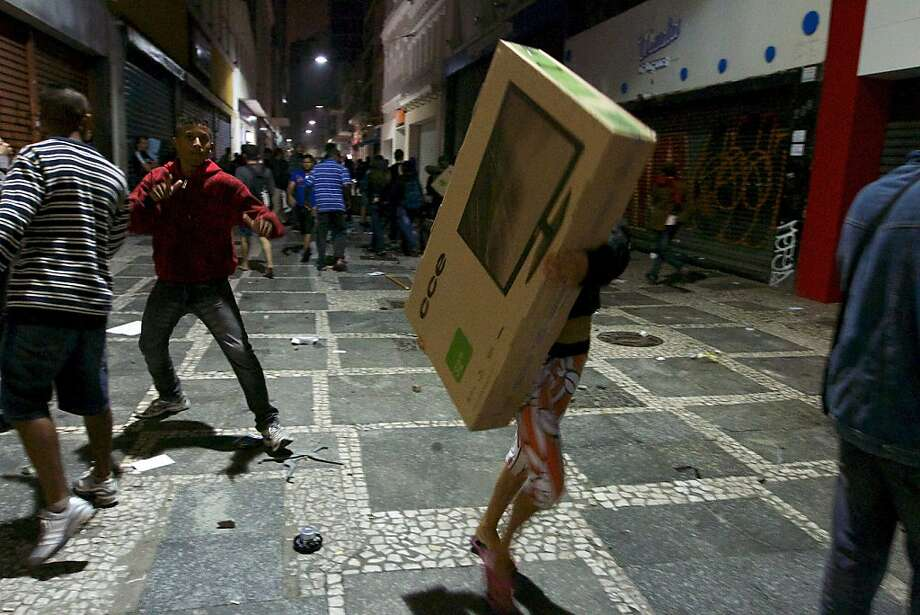Stealing is such an ugly word. We prefer 'liberated from the tyranny of capitalism':While some youths protest transit fare increases in Sao Paulo, others take the opportunity to loot the city's shops. Photo: Daniel Guimaraens, AFP/Getty Images