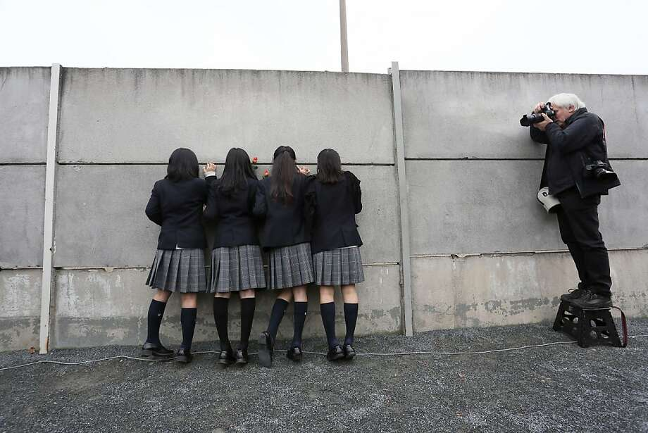 A photographer snaps Japanese high school girls peeping through a 