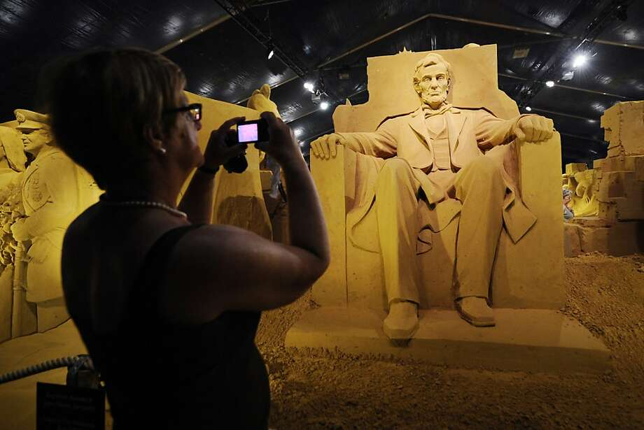 Lincoln memorable:A woman snaps cell-phone photos of a silicon Abraham Lincoln during the Sand Sculpture Festival in Blankenberg, Belgium. Photo: John Thys, AFP/Getty Images