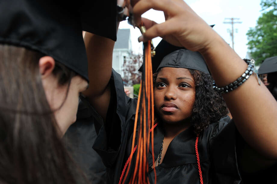 Early Care & Education student Lourdes Ortiz helps fellow graduate Michayla Reyes adjust her cap prior to commencement for the Bullard-Havens Technical High School Class of 2013, held at the Klein Memorial Auditorium, in Bridgeport, Conn. June 19th, 2013. Photo: Ned Gerard / Connecticut Post