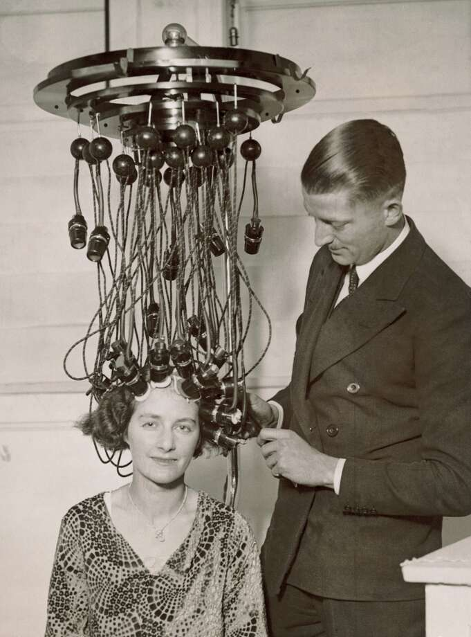 Latest hairstyles and hairdresser equipment at the Hairdressing Fair of Fashion in the White City Hall in London. Photography. 1935.