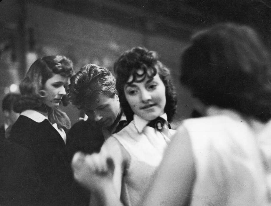 A 'Teddy Girl' dances with a friend at the Mecca Dance Hall, Tottenham, London, 29th May 1954. She wears the high collar with cameo brooch which is typical of the style.
