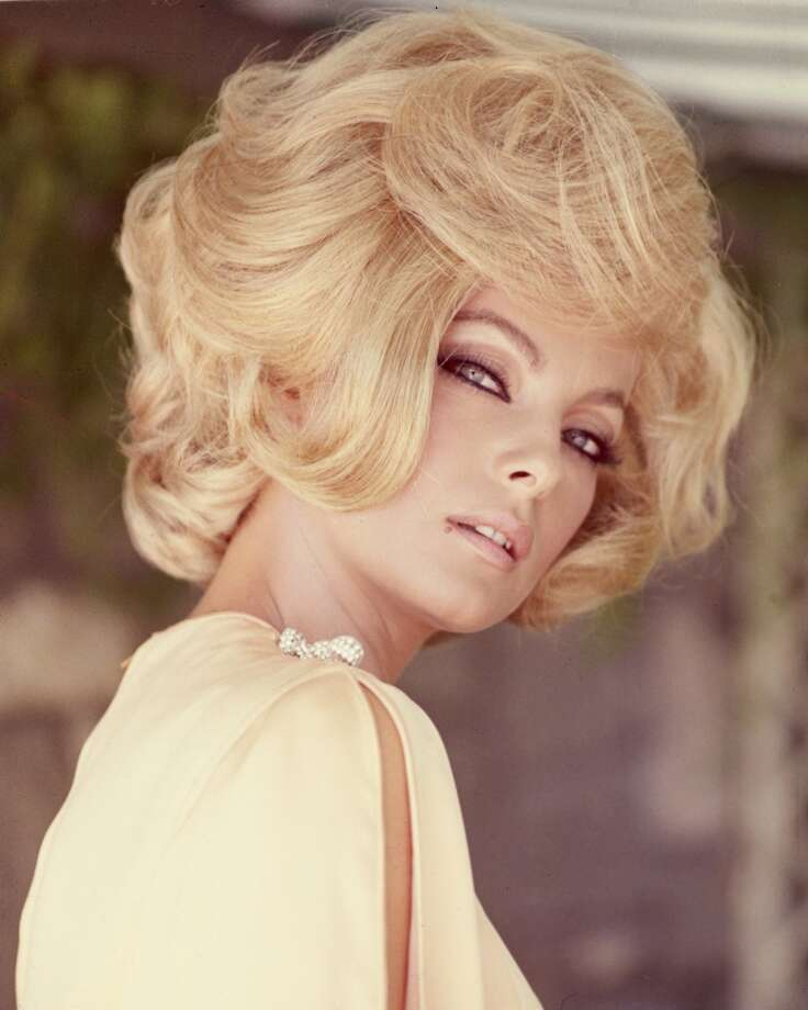 Virna Lisi, Italian actress, wearing a yellow top with slashed sleeves, with a blonde bouffant hairstyle, circa 1960. )
