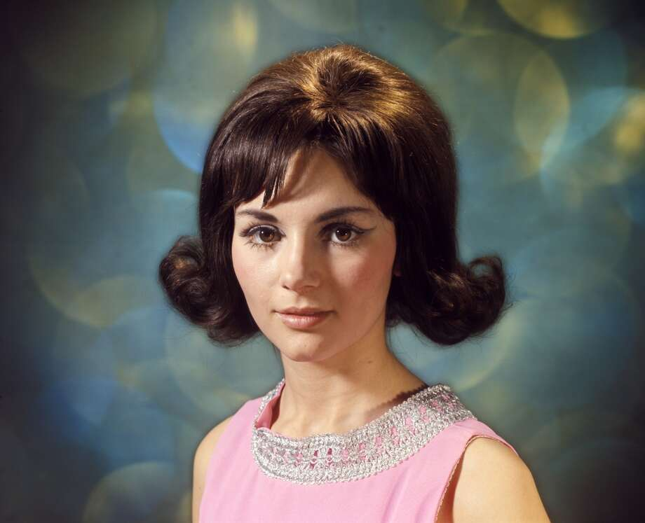 Portrait of brunette woman with flip hairstyle.