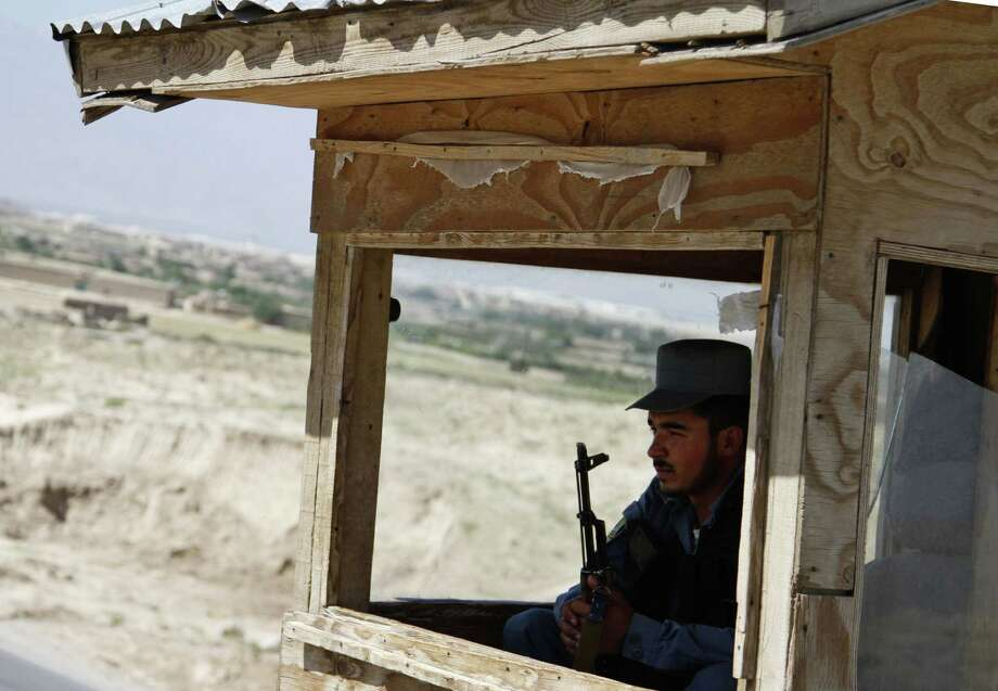 """An Afghan policeman overlooks a checkpoint. Afghan President Hamid Karzai says, """"The way the Taliban office was opened in Qatar and the messages which were sent from it was in absolute contrast with all the guarantees that the United States of America had pledged."""" Photo: Ahmad Jamshid / Associated Press"""