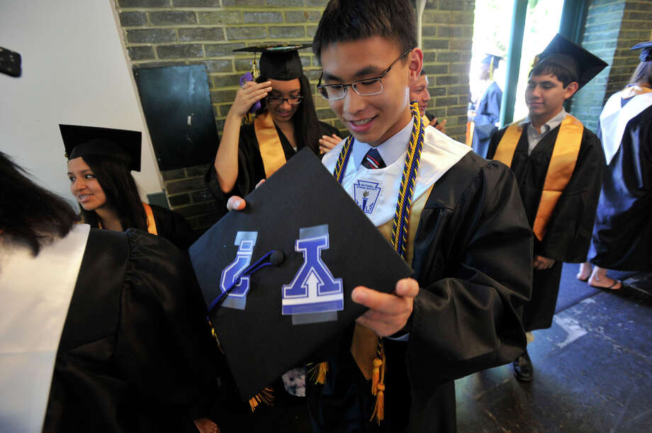Cameron Yick puts on his cap before the Academy of Information Technology and Engineering commencement ceremony at Rippowam Middle School in Stamford on Wednesday, June 19, 2013. Photo: Jason Rearick / Stamford Advocate