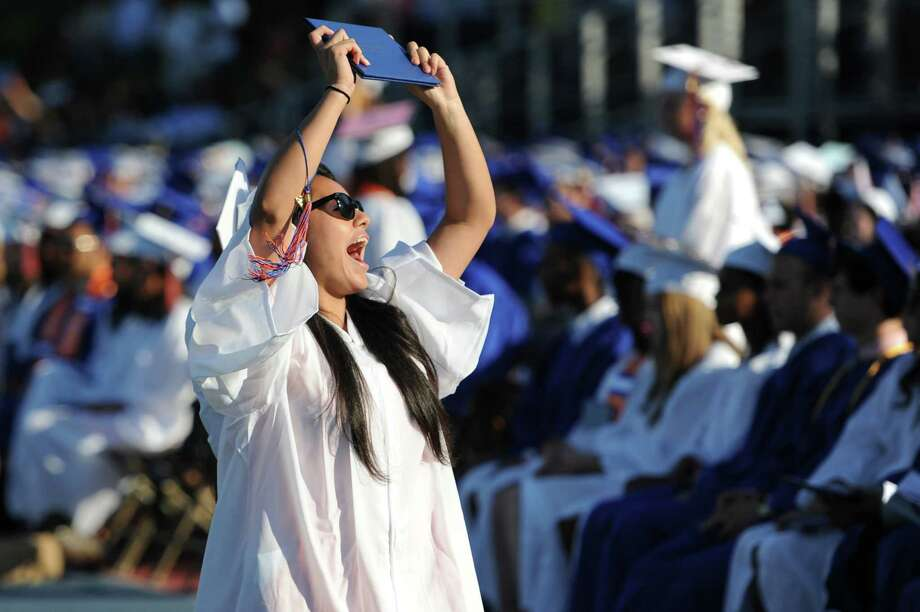 Yvonne Sanchez holds her diploma in the air after crossing the stage at the Danbury High School commencement in Danbury, Conn. on Wednesday, June 19, 2013.  639 Danbury seniors graduated at this year's ceremony. Photo: Tyler Sizemore / The News-Times