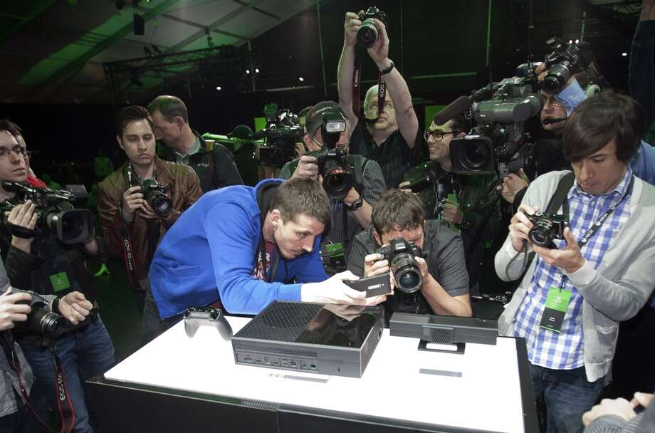 Members of the media take photos and shoot video at the unveiling for Microsoft Corp.'s first new Xbox in almost eight years in Redmond, Washington, U.S., on Tuesday, May 21, 2013. The player, called Xbox One, is set to go on sale later this year and will use voice commands and motion sensing to recognize users and let them switch seamlessly between games, live TV and Skype video calling.