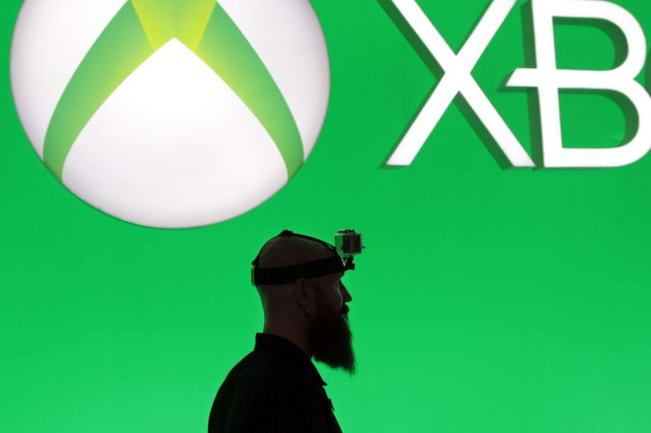 A man wearing a Woodman Labs Inc. GoPro camera on his head walks past Microsoft Corp. Xbox signage during the E3 Electronic Entertainment Expo in Los Angeles, California, U.S., on Tuesday, June 11, 2013. Microsoft, which has led console sales in the past couple of years with the Xbox 360, introduced the $499 Xbox One, which goes on sale in November.
