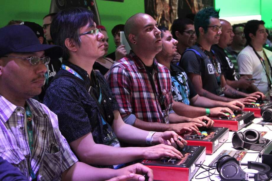 Attendees play Killer Instinct on the Microsoft Corp. Xbox One video game console at the Xbox booth during the E3 Electronic Entertainment Expo in Los Angeles, California, U.S., on Tuesday, June 11, 2013. Microsoft, which has led console sales in the past couple of years with the Xbox 360, introduced the $499 Xbox One, which goes on sale in November.