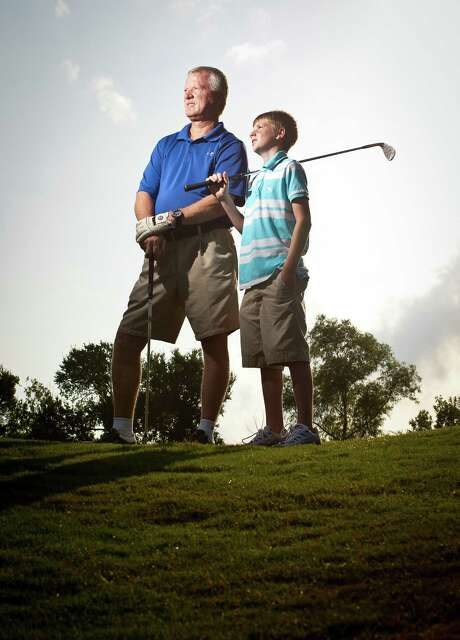 Lonnie Whitener and his son, Zach, stand at the sixth hole of the River Pointe Golf Club in Richmond, where each hit a hole in one on Father's Day. Photo: Nick De La Torre, Staff / © 2013  Houston Chronicle