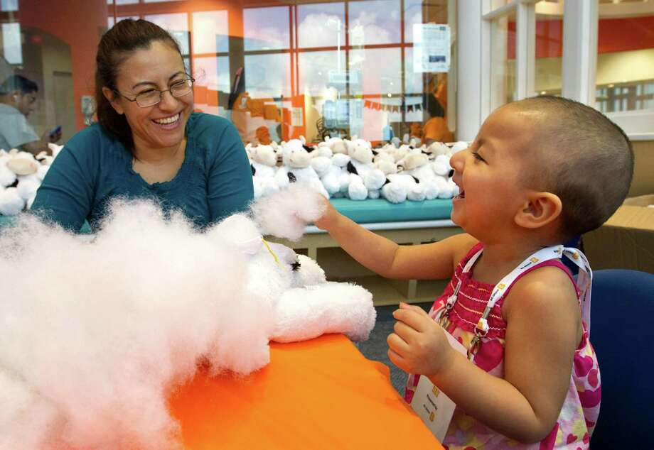 Karina Hernandez laughs with her daughter Stephanie Hernandez, 2, as they build a stuffed animal cow during the Build-A-Buddy activity at Camp Periwinkle Day at Texas Children's Hospital, Wednesday, June 19, 2013, in Houston. Photo: Cody Duty, Houston Chronicle / © 2013 Houston Chronicle