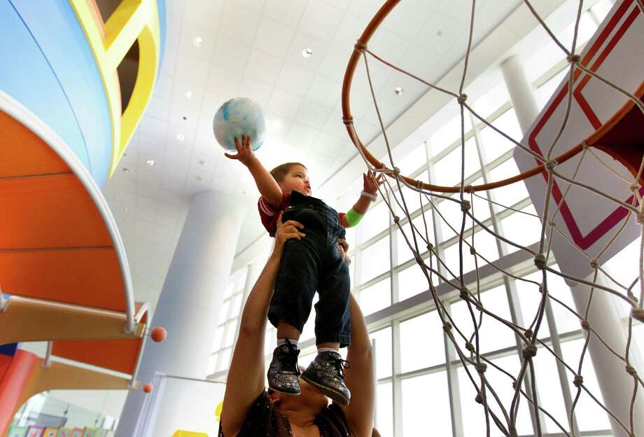 Cruskaya Joyas carries her 18-month-old son, Diego Joyas, to shoot a basket during Camp Periwinkle Day at Texas Children's Hospital, Wednesday, June 19, 2013, in Houston. Photo: Cody Duty, Houston Chronicle / © 2013 Houston Chronicle