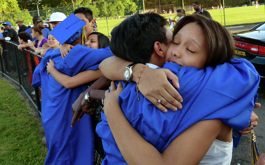 Graduate Andres Batista gets a hug from his close friend Sabrina Martinez, after Warren Harding High School's 87th Annual Commencement ceremony which was held at Central High School's Kennedy Stadium in Bridgeport, Conn. on Wednesday June 19, 2013. Photo: Christian Abraham / Connecticut Post