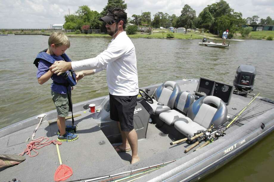Volunteer Laith Peters, right, helps family friend Elijah Krasek, 7, left,  with a life jacket during event with Lake Houston Sports & Recreation to distribute 100,000 Florida hybrid bass at Lake Houston. Photo: Melissa Phillip, Houston Chronicle / © 2013  Houston Chronicle