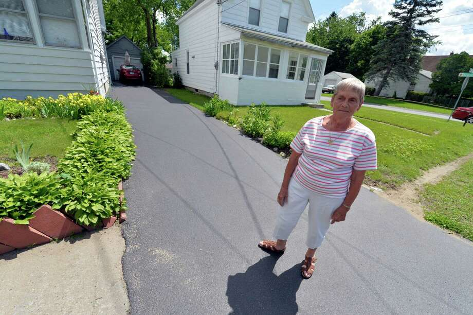 Shirley Gaylord stands on a driveway that has caused her to be fined by the city of Schenectady, which does not allow blacktop over concrete sidewalks. Gaylord believes the citation is unfair, in part because the Albany Street sidewalk does not continue on the adjoining property. (Skip Dickstein / Times Union) Photo: SKIP DICKSTEIN / 10022821A