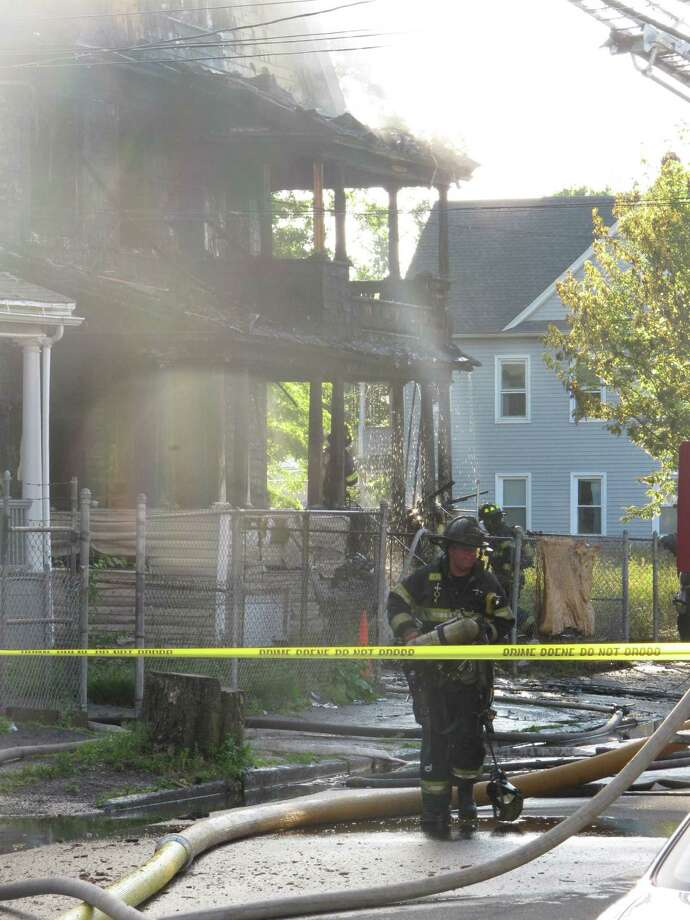 Bridgeport firefighters fight a two-alarm fire that tore through a Poplar Street home Monday evening and led to the hospitalization of two children and two police officers, authorities said. The fire severely damaged the three-story home while hundreds of neighborhood residents looked on. Photo: Staff Photo/Denis J. O'Malley