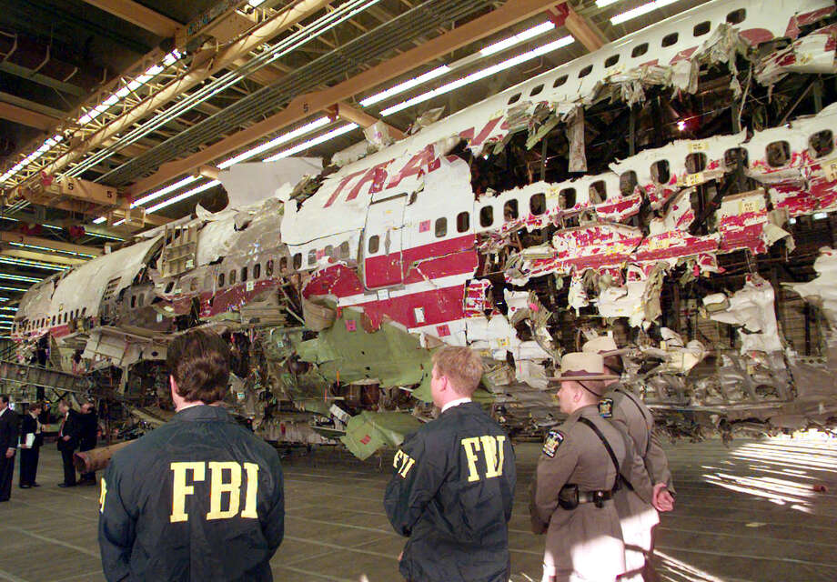 FILE - In this Nov. 19, 1997 file photo, FBI agents and New York state police guard the reconstruction of TWA Flight 800 in Calverton, N.Y. Flight 800 exploded and crashed July 17, 1996 while flying from New York to Paris, killing all 230 people aboard. Former investigators on Wednesday, June 19, 2013 called on the National Transportation Safety Board to re-examine the cause, saying new evidence points to the often-discounted theory that a missile strike may have downed the jumbo jet. (AP Photo/Mark Lennihan, File) Photo: MARK LENNIHAN