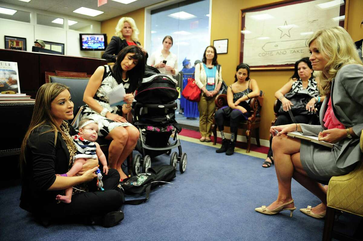 Ashley Cardenas, holding daughter Audrina, 8 months old, talks to a staffer Laura Holland, right, at Sen. John Cornyn's (R-TX) office on Capitol Hill in Washington DC.