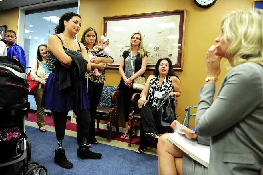 Jamie Schanbaum, 24, who lost her legs to meningitus and Ashley Cardenas, holding daughter Audrina, 8 months old, talk to a staffer Laura Holland, right,  at Sen. John Cornyn's (R-TX) office on Capitol Hill in Washington DC. Photo: Mary F. Calvert, For The Chronicle / © 2013 MARY F. CALVERT