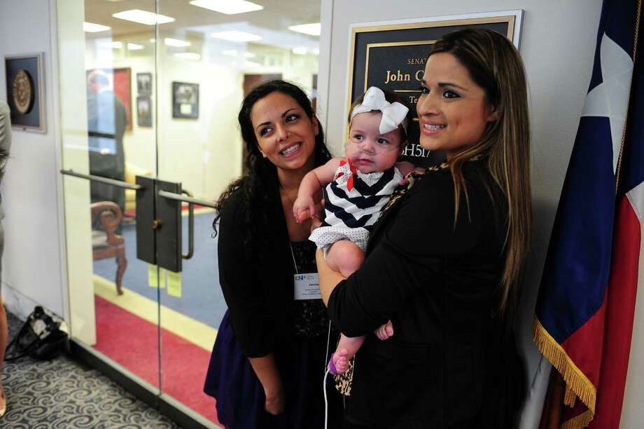 Jamie Schanbaum, 24, who lost her legs to meningitus and Ashley Cardenas, holding daughter Audrina, 8 months old, have their picture taken outside Sen. John Cornyn's (R-TX) office on Capitol Hill in Washington DC. Photo: Mary F. Calvert, For The Chronicle / © 2013 MARY F. CALVERT