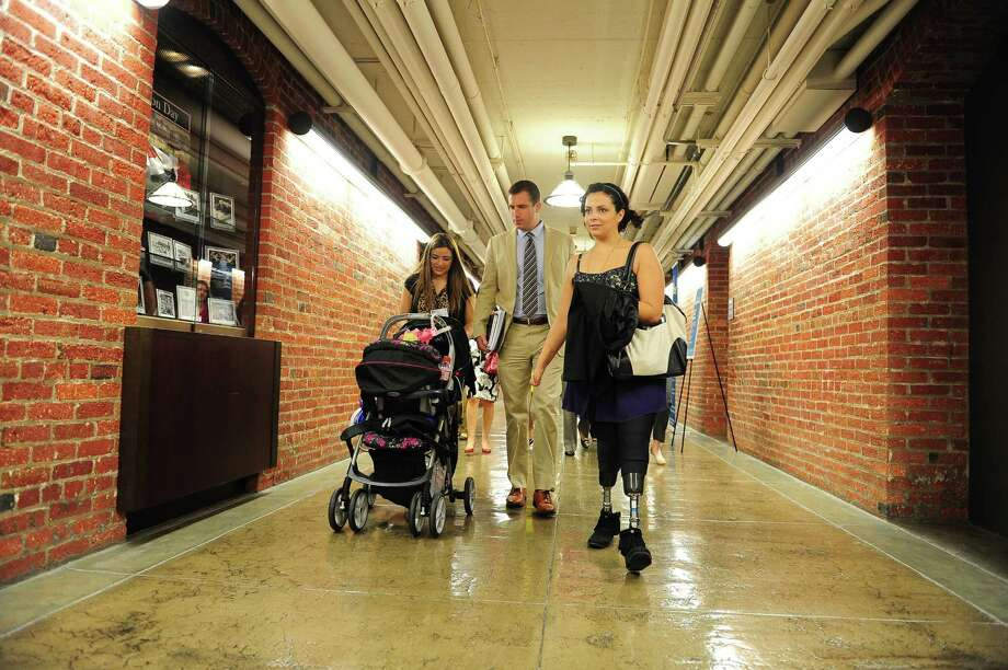 Ashley Cardenas, pushing the stroller of daughter Audrina, 8 months old, walks with Charlie Ellesworth and Jamie Schanbaum, 24, who lost her legs to meningitus on Capitol Hill in Washington DC. Photo: Mary F. Calvert, For The Chronicle / © 2013 MARY F. CALVERT
