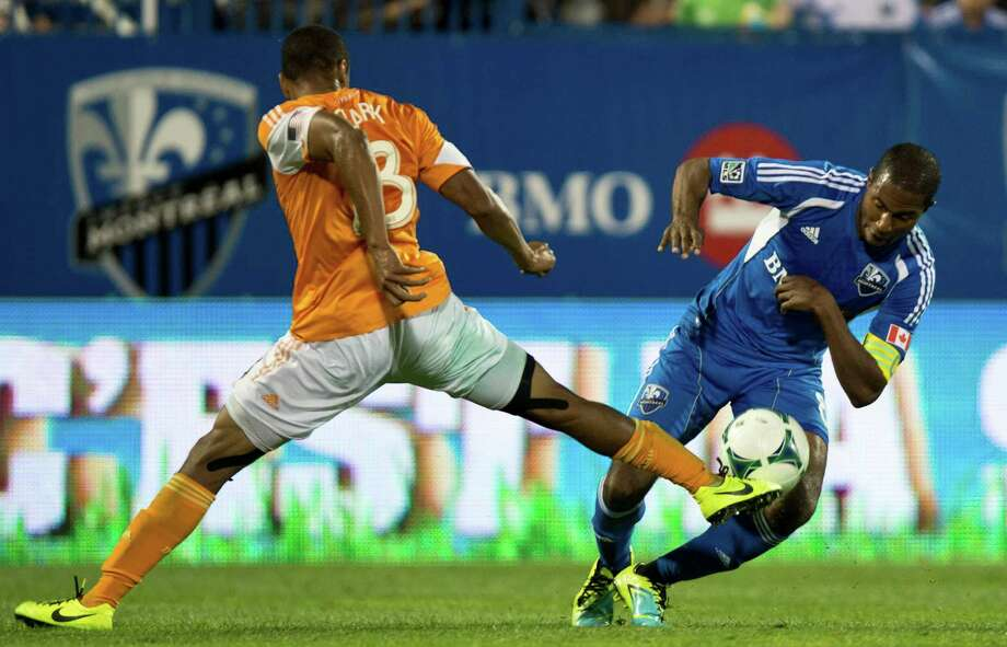 Houston Dynamo's Ricardo Clark, left, kicks the ball away from Montreal Impact's Patrice Bernier during second-half MLS soccer game action on Wednesday, June 19, 2013, in Montreal. (AP Photo/The Canadian Press, Paul Chiasson) Photo: Paul Chiasson, Associated Press / The Canadian Press