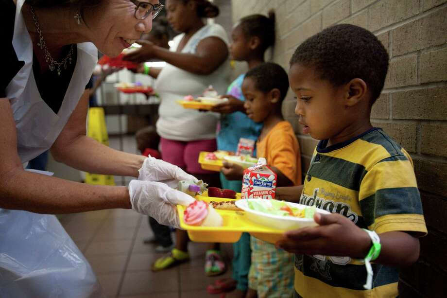 Ikeevion Smith, 3, is handed a tray of pizza and other food as homeless women and children lunch on donated pizza, June 18, 2013 in Houston at Star of Hope. Photo: Eric Kayne, For The Chronicle / ©2013 Eric Kayne
