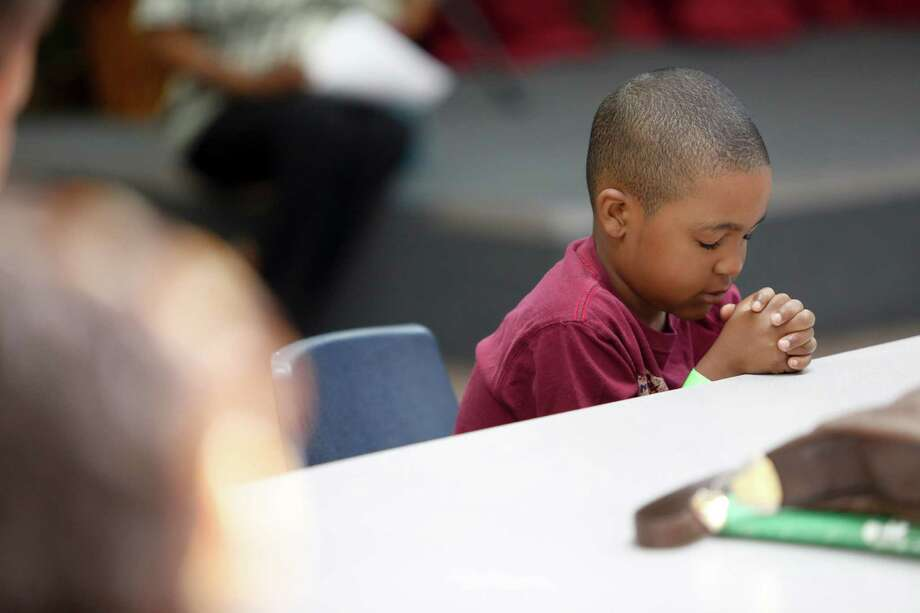 Noah Boyd, 5, prays before eating as homeless women and children lunch on donated pizza, June 18, 2013 in Houston at Star of Hope. Photo: Eric Kayne, For The Chronicle / ©2013 Eric Kayne