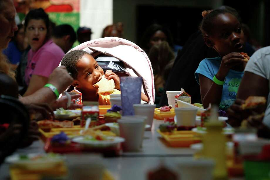 Devonte Walker, 4, eats pizza and other food as homeless women and children lunch on donated pizza, June 18, 2013 in Houston at Star of Hope. Photo: Eric Kayne, For The Chronicle / ©2013 Eric Kayne