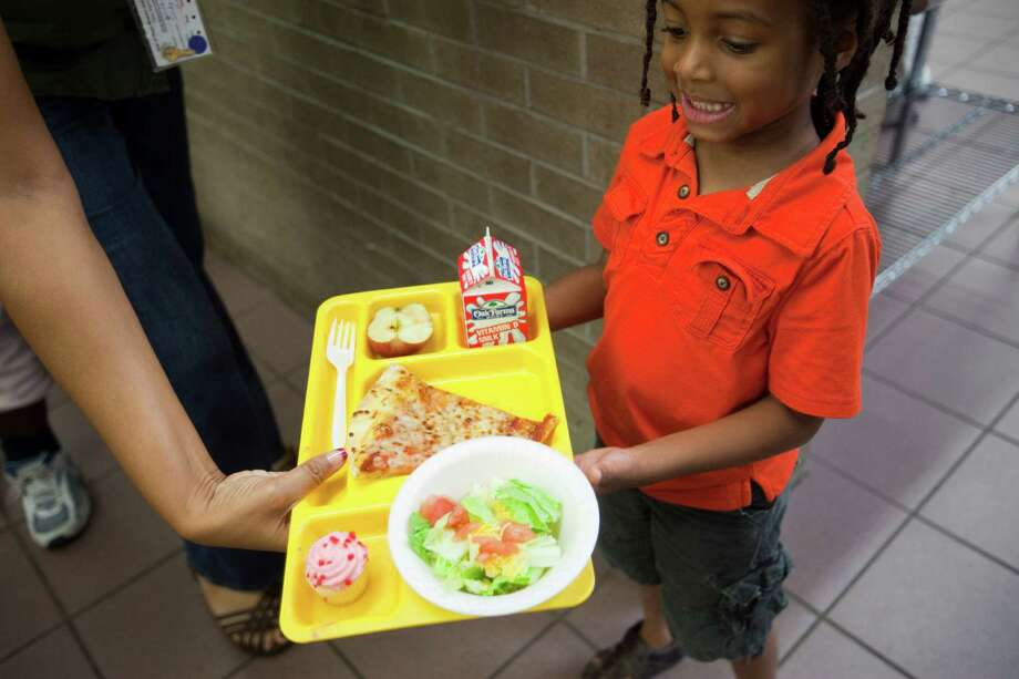 Zion Hooper, 4, is handed a tray of pizza and other food as homeless women and children lunch on donated pizza, June 18, 2013 in Houston at Star of Hope. Photo: Eric Kayne, For The Chronicle / ©2013 Eric Kayne