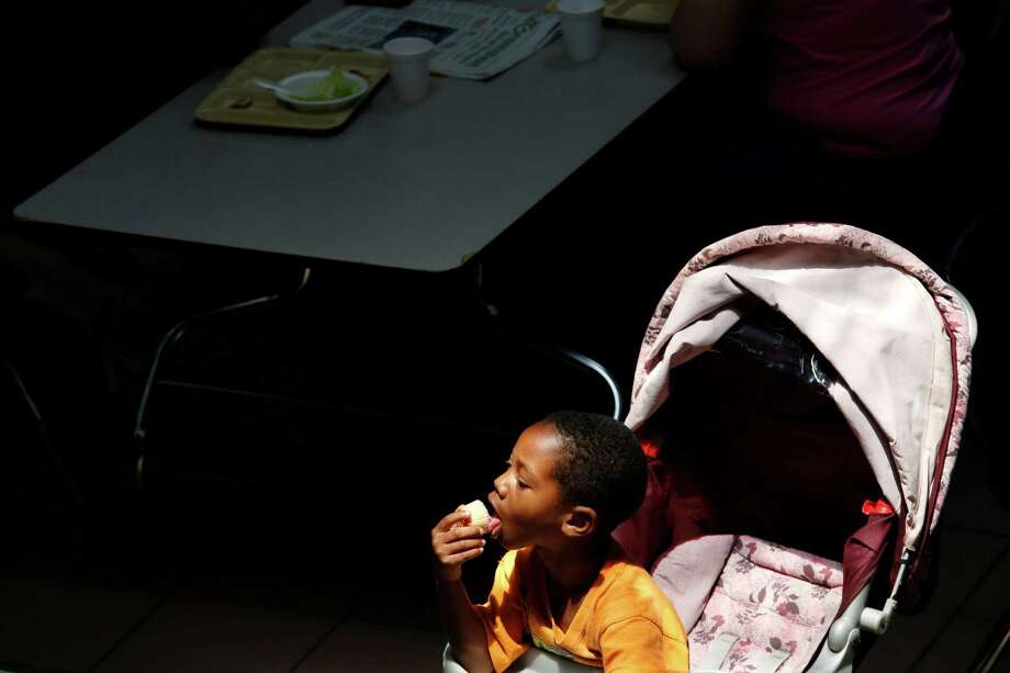 Devonte Walker, 4, licks a cupcake as homeless women and children lunch on donated pizza, June 18, 2013 in Houston at Star of Hope. Photo: Eric Kayne, For The Chronicle / ©2013 Eric Kayne