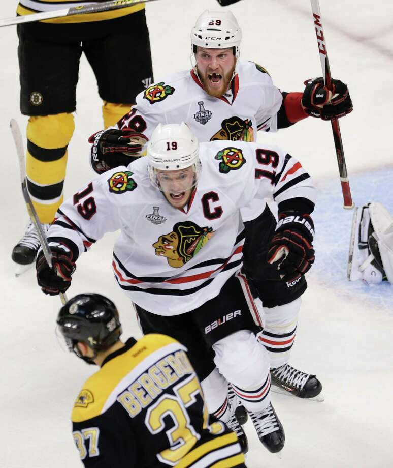 Chicago Blackhawks left wing Bryan Bickell (29) and center Jonathan Toews (19) celebrate the winning goal by Brent Seabrook, not shown, in front of Boston Bruins center Patrice Bergeron (37) during the first overtime period in Game 4 of the NHL hockey Stanley Cup Finals, Wednesday, June 19, 2013, in Boston. Chicago won 6-5. (AP Photo/Charles Krupa) Photo: Charles Krupa, Associated Press / AP
