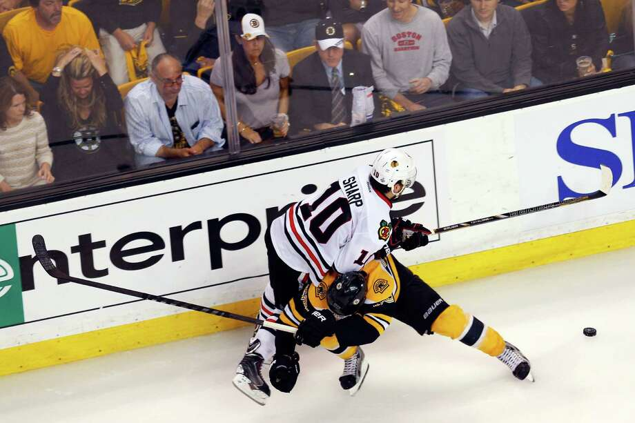 BOSTON, MA - JUNE 19: Johnny Boychuk #55 of the Boston Bruins collides with Patrick Sharp #10 of the Chicago Blackhawks in Game Four of the 2013 NHL Stanley Cup Final at TD Garden on June 19, 2013 in Boston, Massachusetts. Photo: Jim Rogash, Getty Images / 2013 Getty Images