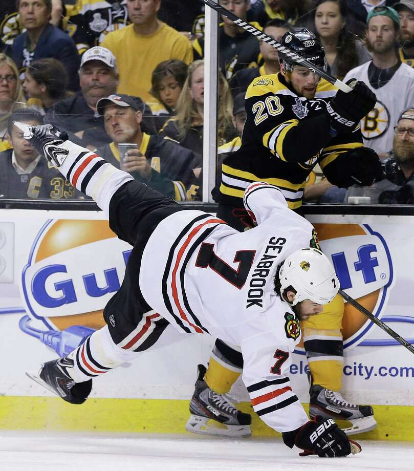 Boston Bruins left wing Daniel Paille (20) checks Chicago Blackhawks defenseman Brent Seabrook (7) to the ice during the second period in Game 4 of the NHL hockey Stanley Cup Finals, Wednesday, June 19, 2013, in Boston. (AP Photo/Elise Amendola) Photo: Elise Amendola, Associated Press / AP