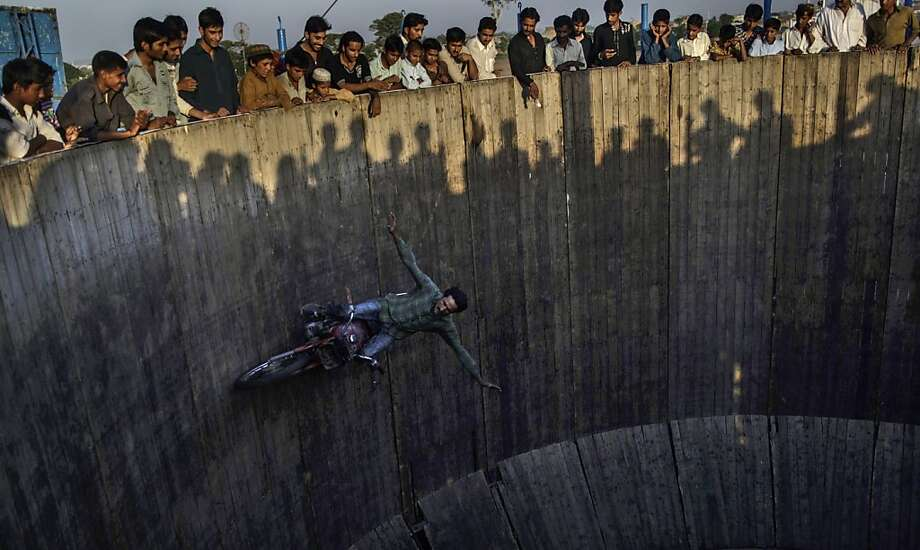 The centrifugal force be with you: An motorcycle acrobat circles the inside of a giant barrel at an 