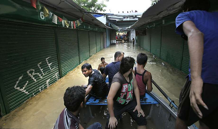 Indian people use a boat to cross a Tibetan market along the banks of the Yamuna River, in New Delhi, India, Wednesday, June 19, 2013. India's prime minister said Wednesday that the death toll from flooding this week in the northern state of Uttrakhand had surpassed 100 and could rise substantially. The flooding has affected several states and the capital, New Delhi, where nearly 2,000 people have been evacuated to government-run camps on higher ground. Authorities there said the situation would ease as the level of the Yamuna River was expected to start receding Thursday afternoon. (AP Photo/Manish Swarup) Photo: Manish Swarup, Associated Press