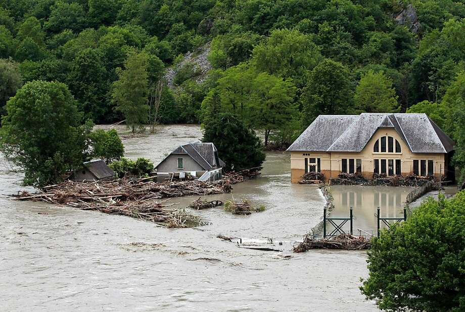 Buildings are surrounded by flood water near Lourdes, southwestern France, Wednesday, June 19, 2013. French rescue services and police are evacuating hundreds of pilgrims from hotels threatened by floodwaters from a rain-swollen river in the Roman Catholic shrine town of Lourdes. (AP Photo/Bob Edme) Photo: Bob Edme, Associated Press