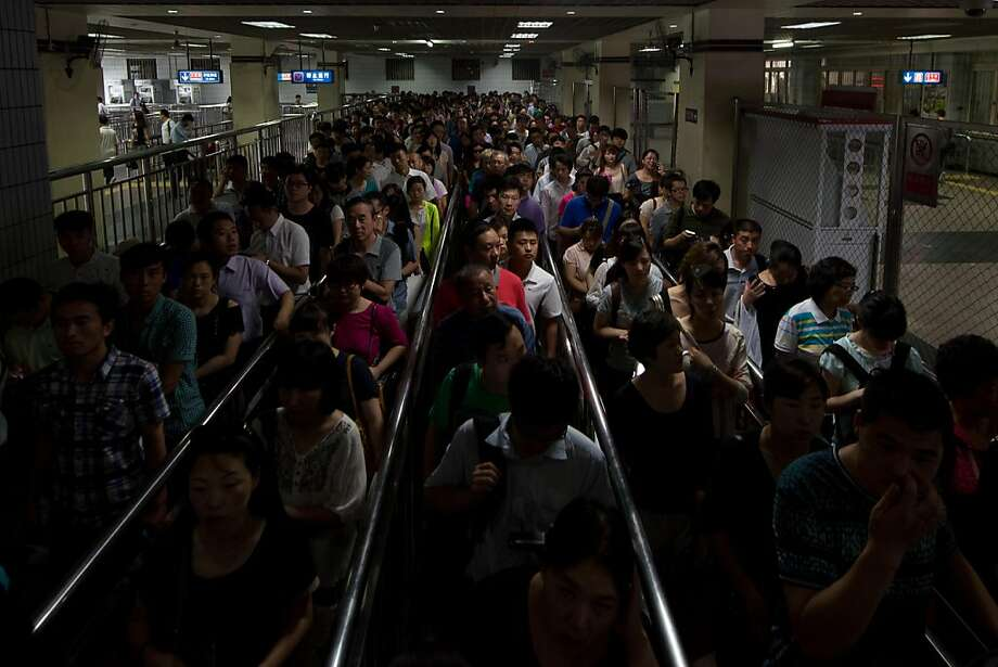 Commuters wait to enter a subway station during the morning rush hour in Beijing on June 19, 2013. Despite some five million private vehicles in Beijing, public transport faces heavy congestion on a daily basis as most of the city's 20 million people head to work. AFP PHOTO / Ed JonesEd Jones/AFP/Getty Images Photo: Ed Jones, AFP/Getty Images