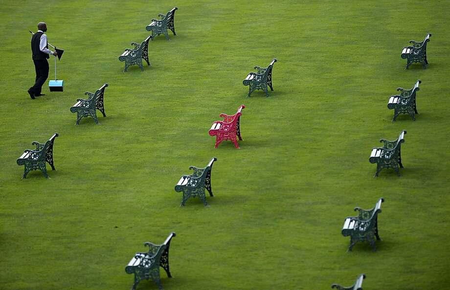 A cleaner walks between the benches on the lawn in front of the grandstand ahead of the start of the second day of Royal Ascot, in Berkshire, west of London, on June 19, 2013. The five-day meeting is one of the highlights of the horse racing calendar. Horse racing has been held at the famous Berkshire course since 1711 and tradition is a hallmark of the meeting. Top hats and tails remain compulsory in parts of the course while a daily procession of horse-drawn carriages brings the Queen to the course. AFP PHOTO / ADRIAN DENNISADRIAN DENNIS/AFP/Getty Images Photo: Adrian Dennis, AFP/Getty Images