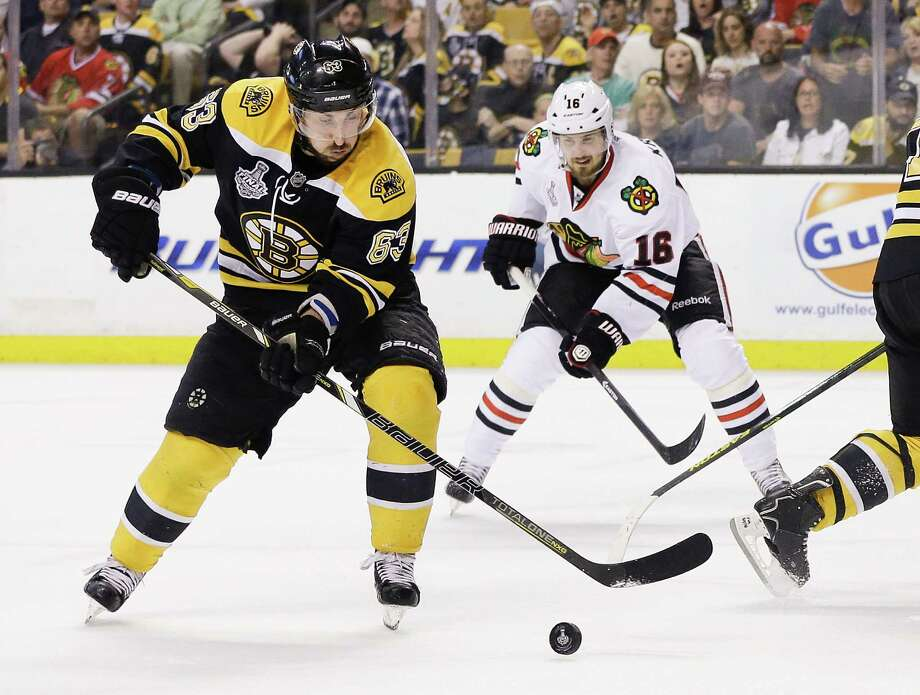 Boston Bruins left wing Brad Marchand (63) moves the puck in front of Chicago Blackhawks center Marcus Kruger (16) during the first period in Game 4 of the NHL hockey Stanley Cup Finals, Wednesday, June 19, 2013, in Boston. (AP Photo/Elise Amendola) Photo: Elise Amendola