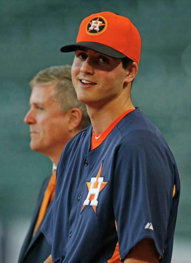 Houston Astros general manager Jeff Luhnow, left, waits on the field alongside first overall draft pick Mark Appel after Appel signed with the team prior to the start of the game between the Milwaukee Brewers and the Houston Astros at Minute Maid Park on June 19, 2013, in Houston, Texas.  (Photo by Scott Halleran/Getty Images) Photo: Scott Halleran