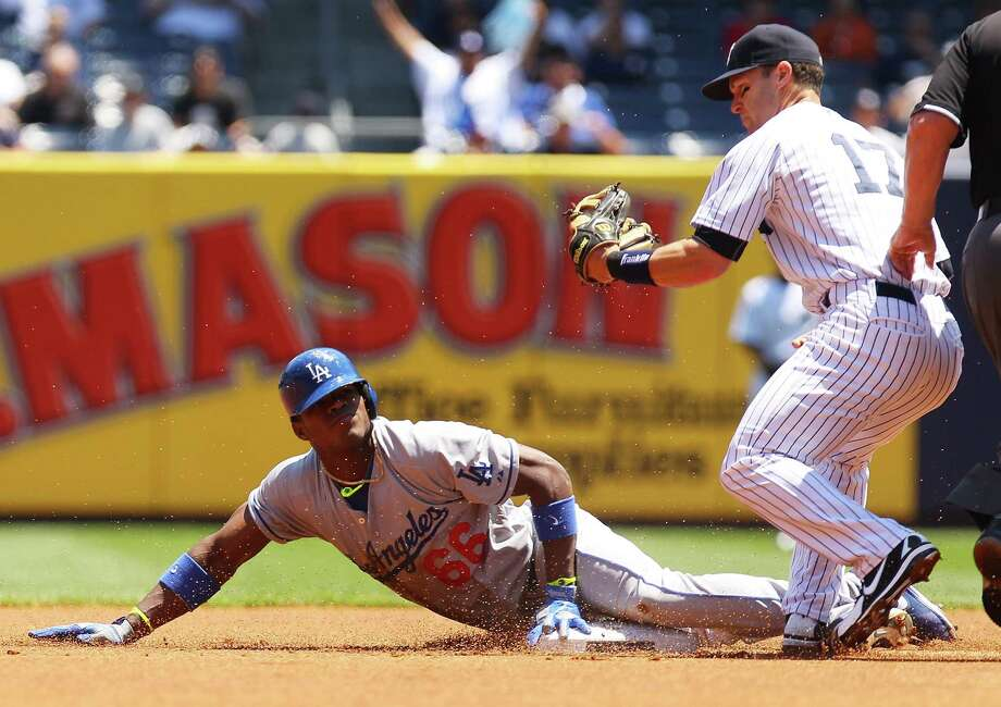 NEW YORK, NY - JUNE 19:  Yasiel Puig #66 of the Los Angeles Dodgers reacts after being thrown out at second trying to strecth a single into a double as Jayson Nix #17 of the New York Yankees looks on in the first inning at Yankee Stadium on June 19, 2013 in the Bronx borough of New York City.  (Photo by Mike Stobe/Getty Images)  *** BESTPIX *** Photo: Mike Stobe