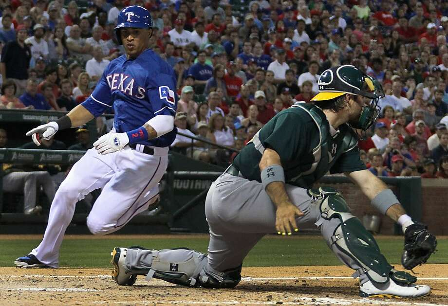 The Texas Rangers' Leonys Martin, left, arrives home with a run in the fifth inning as Oakland Athletics catcher Derek Norris takes the throw at the Rangers Ballpark in Arlington on Wednesday, June 19, 2013, in Arlington, Texas. (Louis DeLuca/Dallas Morning News/MCT) Photo: Louis DeLuca, McClatchy-Tribune News Service